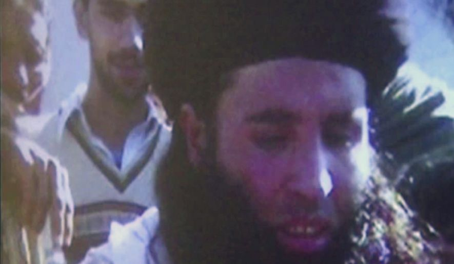 In this file image made from video broadcast on Thursday, Nov. 7, 2013, undated footage of Mullah Fazlullah is shown on a projector in Pakistan. An Afghan defense ministry official says Friday, June 15, 2018, that a U.S. drone strike in northeastern Kunar province killed Pakistan Taliban chief Mullah Fazlullah. Pakistan has been hunting Fazlullah for several years and has repeatedly said he was plotting attacks on Pakistan from safe havens in Afghanistan. (AP Photo via AP Video, File)