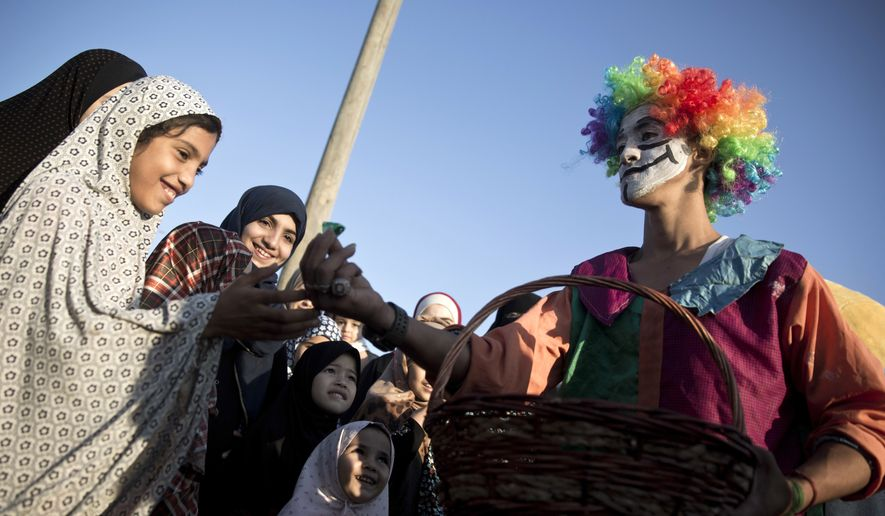 A Palestinian man wearing as a clown presents candies to Muslim girls during Eid al-Fitr prayers, marking the end of the holy fasting month of Ramadan, in Eastern Gaza City, Friday, June 15, 2018. (AP Photo/Khalil Hamra)