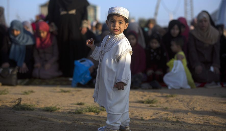 A Palestinian boy wearing a traditional uniform stands in front of Muslim women performing Eid al-Fitr prayers, marking the end of the holy fasting month of Ramadan, in Eastern Gaza City, Friday, June 15, 2018. (AP Photo/Khalil Hamra)