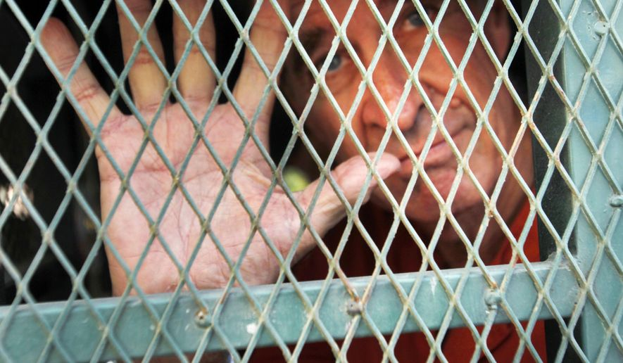 Australian filmmaker James Ricketson gestures from inside a prison truck upon his arrival at Phnom Penh Municipal Court in Phnom Penh, Cambodia, Friday, June 15, 2018. The court on Friday delayed its hearing on Ricketson who has been held in prison since being charged with spying for an unspecified foreign country, after flying a drone at a political rally in June 2017. (AP Photo/Heng Sinith)