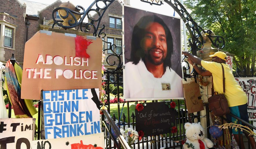 FILE - In this July 24, 2016, file photo, a photo of Philando Castile hangs on the gate of the governor's residence in St. Paul, Minn., as protesters demonstrate against the July 2016, shooting death of Castile by a St. Anthony police officer making a traffic stop in Falcon Heights, Mich. The St. Anthony Police Department announced new goals, Thursday, June 14, 2018, to help rebuild community trust following Castile's death. (Scott Takushi/Pioneer Press via AP)