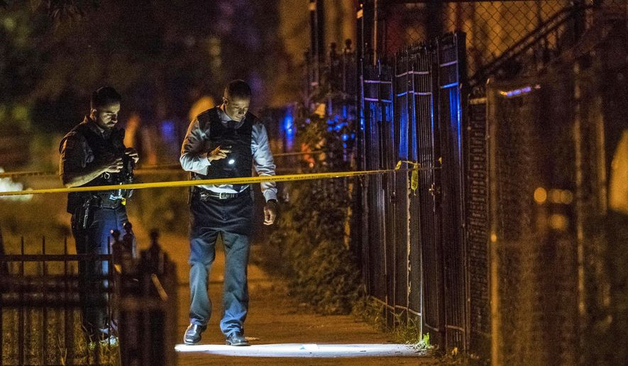 In this Thursday, June 14, 2018 photo, Chicago Police officers investigate the scene where two people were shot in Chicago. A 12-year-old Michigan girl spending the summer in Chicago was fatally shot at the scene, hours after attending a cousin's eighth-grade graduation. Family members at the hospital identified the girl as She'nyah O'Flynn of Covert, Michigan. She and a man who was injured were apparently unintended victims of gunfire from a nearby party. Police say there have been no arrests. (Tyler LaRiviere /Chicago Sun-Times via AP)