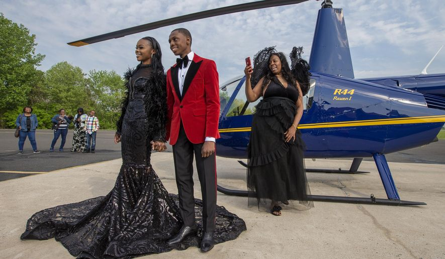 Saudia Shuler, right, films her son, Nieme Brooker with his date Tiana Johnson in this James Bond-style prom send-off on May 12, 2018. They attended the Penn Wood prom later that evening. (Charles Fox /The Philadelphia Inquirer via AP)