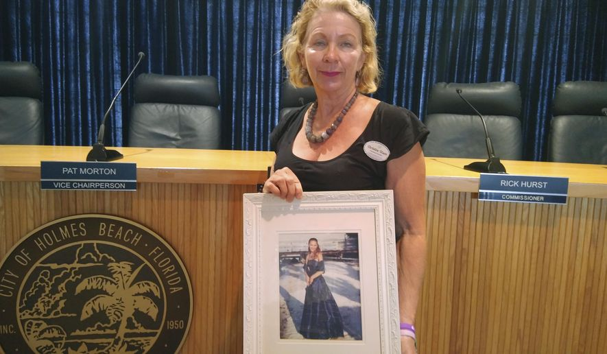 Christine Olson holds a prom picture of her daughter, Tiffany, who was killed in an accident in 2005. Her death sparked a non-profit encouraging people to register contact information to assist law enforcement. (Chris Anderson/Sarasota Herald-Tribune via AP)