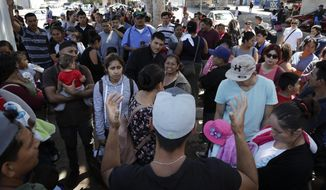 In this June 13, 2018 photo, an organizer, foreground, speaks to families as they wait to request political asylum in the United States, across the border in Tijuana, Mexico. In Tijuana, Latin Americans fleeing drug violence in their countries are camped out and waiting to apply for U.S. asylum - undeterred by the new directive from Attorney General Jeff Sessions this week to bar victims of gang violence from qualifying. (AP Photo/Gregory Bull)