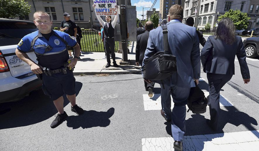 Jonathan Wilson, 33, of Scranton, Pa., holds a sign outside of a Lackawanna College were U.S. Attorney Jeff Sessions spoke on immigration policy and law enforcement actions, Friday, June 15, 2018, in Scranton, Pa. Attendees who took part in listening to the speech cross the street at right. (Butch Comegys/The Times-Tribune via AP)