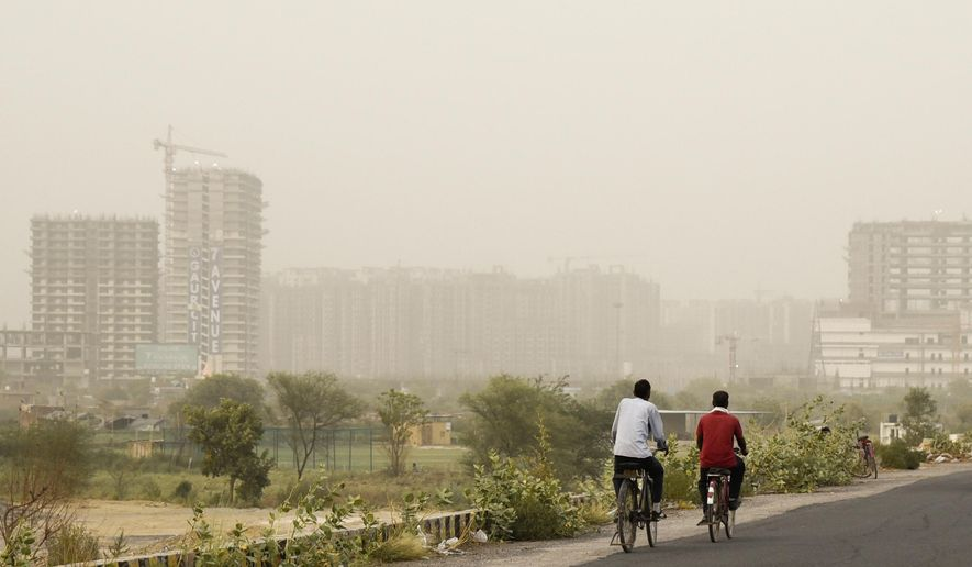 Cyclists pedal on a road enveloped by a thick haze of dust in Greater Noida, on the outskirts of New Delhi, India, Thursday, June 14, 2018. The Indian capital region experienced severe levels of pollution for the third straight day on Thursday. Over the past two years, New Delhi has earned the dubious distinction of being one of the world's most polluted cities. (AP Photo/R S Iyer)