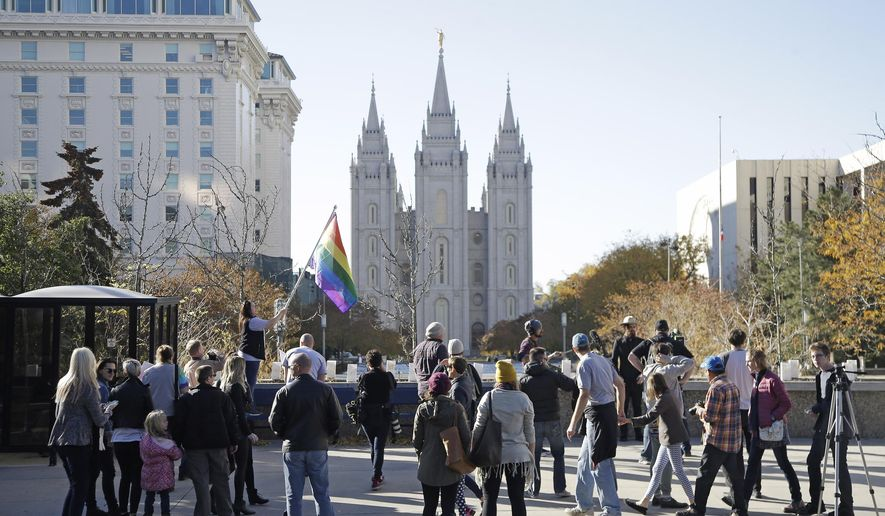 FILE - In this Nov. 14, 2015, file photo, people walk past the Salt Lake Temple after mailing resignation letters during a mass resignation from the Church of Jesus Christ of Latter-day Saints in Salt Lake City. The Mormon church's massive genealogical database will begin accepting submissions of names of people from same-sex relationships sometime next year. The move doesn't foreshadow any change to long-standing church opposition to gay marriage, but it is being done to ensure the databank has as much information as possible for researchers, according to a statement from The Church of Jesus Christ of Latter-day Saints. (AP Photo/Rick Bowmer, File)