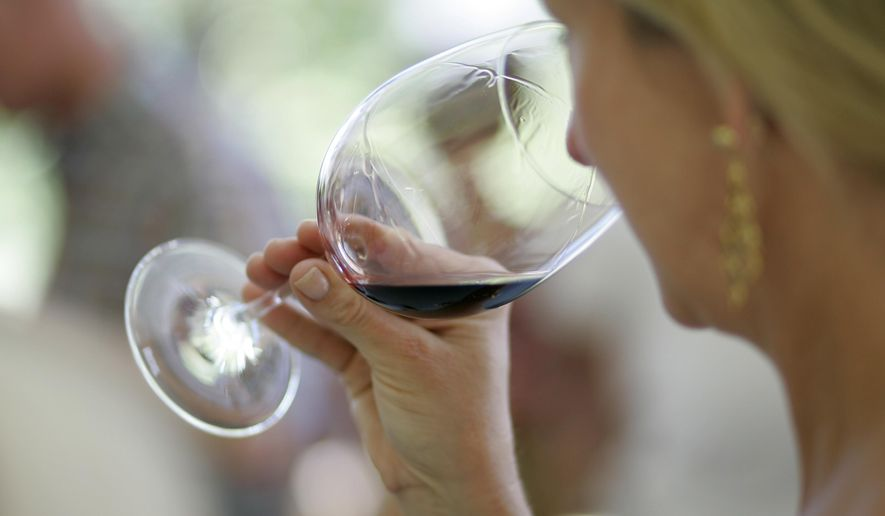 A woman evaluates the aroma of a wine in California on June 7, 2008. (Associated Press) **FILE**