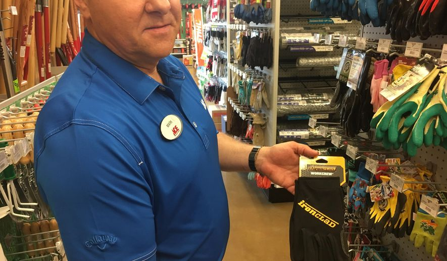 In this Thursday, June 14, 2018 photo, Mark Driscoll, owner of the Ace Hardware in Sugar Grove, Ill., holds a pair of gloves like the type he tried on recently and discovered a man's ring in one of the fingers. He's now trying to find the owner of the ring but so far has had no luck. (Denise Crosby/Chicago Tribune via AP)