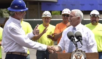 Frank Rewold, left, president and CEO of Frank Rewold & Son, Inc., gives Vice President Mike Pence a thumbs up after introducing Pence at a ceremony at the company's new office building under construction in Rochester, Friday, June 15, 2018 (Todd McInturf/Detroit News via AP)