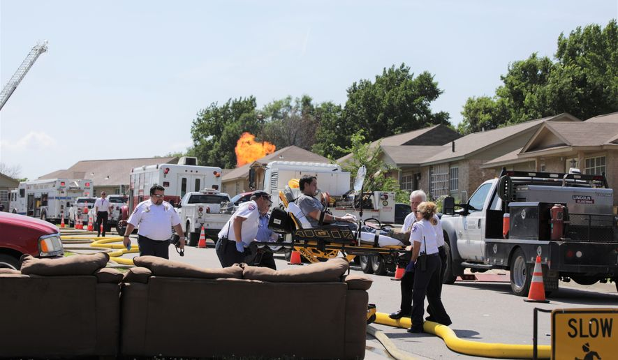 Emergency response crews work to shut off a ruptured gas line and extinguish a resulting fire while extracting injured people from the scene in Tulsa, Okla. Officials say the firefighter, a bystander and three Oklahoma Natural Gas employees were hurt.  (Harrison Grimwood/Tulsa World via AP)