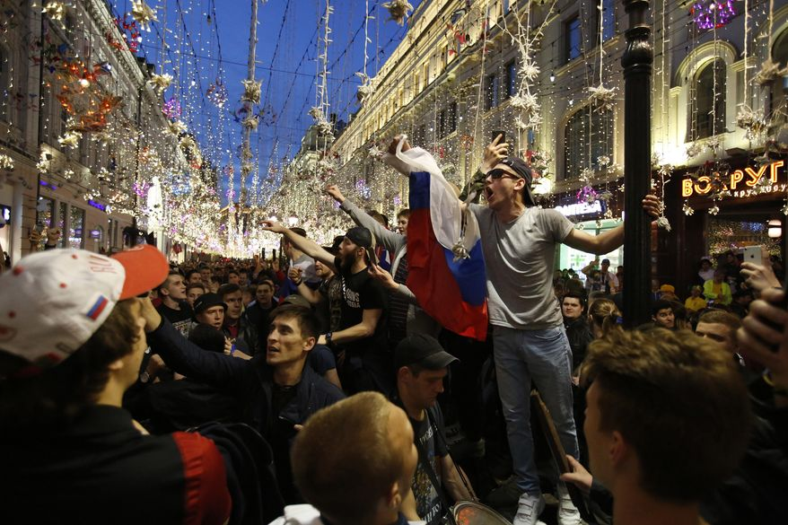 Russia fans celebrate in Nikolskaya street after their team defeated Saudi Arabia 5-0 in the opening match of the 2018 soccer World Cup, in Moscow, Russia, Thursday, June 14, 2018.(AP Photo/Rebecca Blackwell)