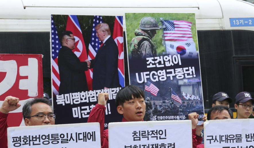 "Members of People's Democratic Party shout slogans during a rally to oppose military exercises between the United States and South Korea near the U.S. Embassy in Seoul, South Korea, Friday, June 15, 2018. U.S. President Donald Trump promised to end ""war games"" with South Korea, calling them provocative, after meeting North Korean leader Kim Jong-un earlier this week. The signs read "" Stop Ulchi Freedom Guardian (UFG) exercises and withdrawal of U.S. troops."" (AP Photo/Ahn Young-joon)"