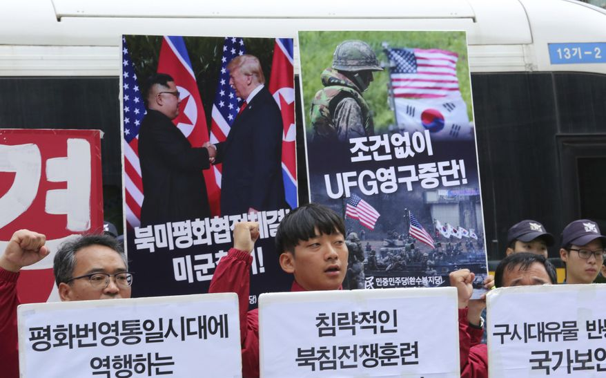 """Members of People's Democratic Party shout slogans during a rally to oppose military exercises between the United States and South Korea near the U.S. Embassy in Seoul, South Korea, Friday, June 15, 2018. U.S. President Donald Trump promised to end """"war games"""" with South Korea, calling them provocative, after meeting North Korean leader Kim Jong-un earlier this week. The signs read """" Stop Ulchi Freedom Guardian (UFG) exercises and withdrawal of U.S. troops."""" (AP Photo/Ahn Young-joon)"""