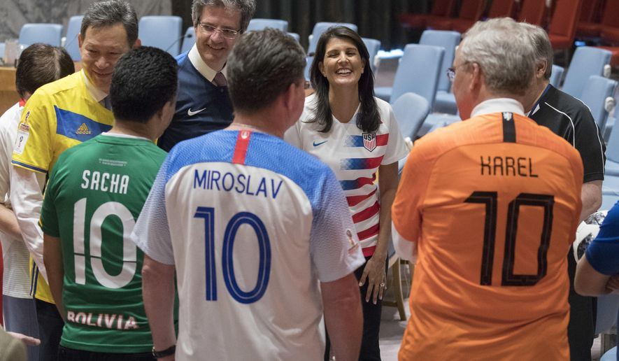American Ambassador to the United Nations Nikki Haley, center, speaks to other members of the Security Council before posing for a photo wearing the jerseys of their country's soccer teams, Thursday, June 14, 2018, at United Nations headquarters. Russian Ambassador to the United Nations Vassily Nebenzia, who is the current president of the Security Council, organized the photo op in honor of the first day of the World Cup Soccer championship. (AP Photo/Mary Altaffer)