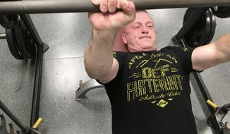 In this May 15, 2018, photo, Richard Ojeda lifts weights at a gym in Logan, W.Va. Ojeda is decorated with military medals and 26 tattoos and can bench presses 300 pounds. The retired Army paratrooper doesn't fit the typical profile of the ideal candidate for Congress. Ojeda, a Democratic state senator, is running against Republican Delegate Carol Miller in November for West Virginia's 3rd District seat. (AP Photo/John Raby)