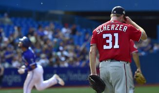 Toronto Blue Jays' Devon Travi, left, rounds the bases after hitting a two-run home run against the Washington Nationals starting pitcher Max Scherzer (31) during the fifth inning inning of a baseball game in Toronto on Saturday, June 16, 2018. (Frank Gunn/The Canadian Press via AP) **FILE**
