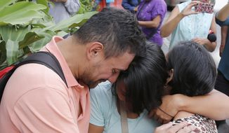 Barbara Barca, center, a survivor of the stampede at a crowded nightclub, is hugged by relatives as they leave police headquarters in Caracas, Venezuela, Saturday, June 16, 2018. Venezuela's government says 17 people were killed early Saturday after a tear gas device was set off during a nightclub brawl in the capital, leading hundreds of people to flee. (AP Photo/Ariana Cubillos)