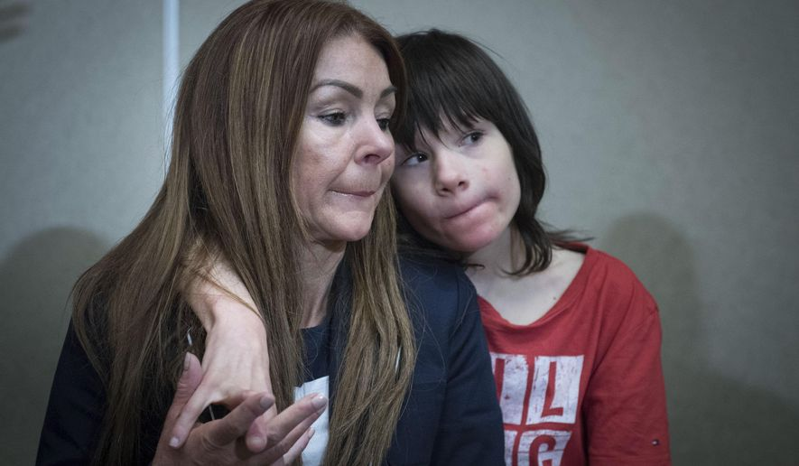 FILE - In this June 11, 2018 file photo, Billy Caldwell sits with his mother Charlotte. The British government on Saturday June 16, 2018, changed course over a case concerning the use of cannabis oil, saying an epileptic boy can be treated with it after his mother said he needed it to survive severe seizures. (Stefan Rousseau/PA via AP, File)