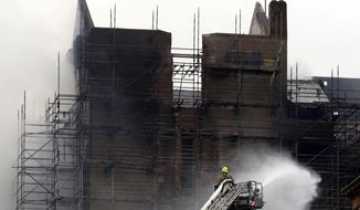 Firefighters at work at the Mackintosh Building at the Glasgow School of Art on Saturday June 16, 2018. Firefighters sought to limit damage to the historic Glasgow School of Art Saturday, after a dramatic fire that ravaged it spread to neighboring properties and led to several evacuations. (Andrew Milligan/PA via AP)