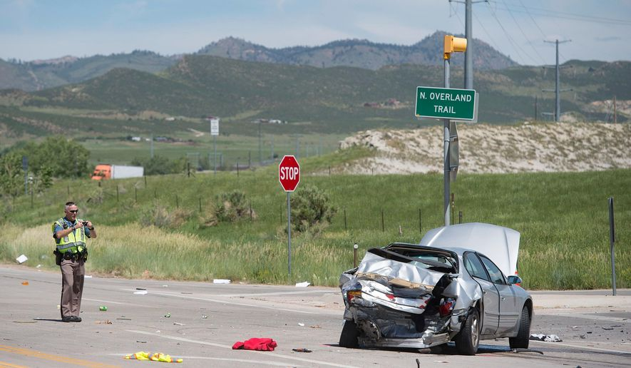 """In this Thursday, June 14, 2018 photo, a Colorado State Patrol trooper takes photos of a car involved in a crash with two other vehicles in Fort Collins, Colo. The time between Memorial Day and Labor Day is often referred to as the """"deadliest 100 days,"""" and Colorado Department of Transport Highway Safety Manager Glenn Davis partially attributes the increase in crashes to more people on the roads. (Austin Humphreys/The Coloradoan via AP)"""