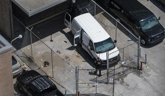 Evidence markers dot the pavement just outside the Wyandotte County courthouse, Friday, June 16, 2018, in Kansas City, Kan. Authorities say one sheriff's deputy is dead and another is critically wounded after they were overcome by an inmate while driving a transport vehicle near the courthouse. (The Kansas City Star via AP)