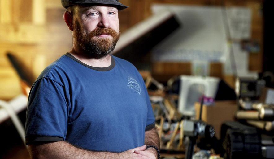 "Portrait of Nathan Brown in his home in Kalispell, Montana on Wednesday, June 6, 2018. Brown, who has survived homelessness, war, post-traumatic stress disorder and an attempted suicide, wears a hat with a badge that reads, ""Bomb Squad: If you see me running, try to keep up"" reminiscent of his time working in explosive ordnance disposal for the U.S. Army. (Brenda Ahearn/Daily Inter Lake via AP)"
