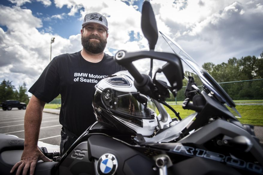 In this Saturday, June 9, 2018 photo, Jeff Shepard, a retired police officer and firefighter, poses in Federal Way, Wash. Shepard developed Post-Traumatic Stress Disorder after he was involved in an ambush shooting in 2012. He is riding across the country on his motorcycle and meeting with different police departments to see how they are helping officers that may have developed PTSD. (Joshua Bessex /The News Tribune via AP)