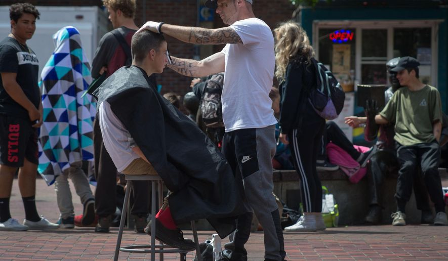 In this May 30, 2018 photo, Jacob Lucas, right, who is recovering from addiction and was once homeless offers a free haircut to Tyler Campbell in Kesey Square while he waits to get his hair cutting license in Eugene, Ore. (Brian Davies/The Register-Guard via AP)