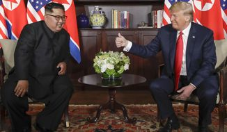 U.S. President Donald Trump gives North Korean leader Kim Jong Un a thumbs up during their meeting at a resort on Sentosa Island in Singapore on Tuesday, June 12, 2018. (AP Photo/Evan Vucci)