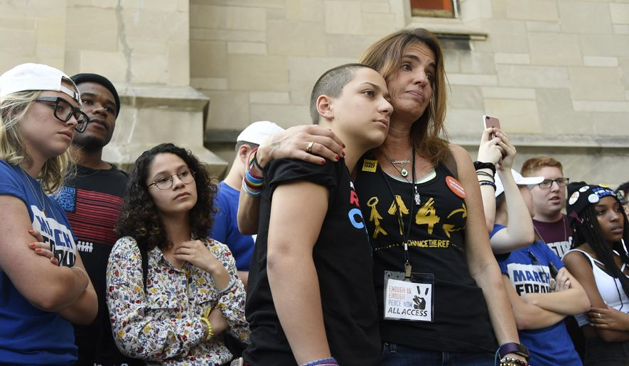 Parkland student activist Emma Gonzalez, center left, hugs Patricia Oliver before a peace rally and march, Friday, June 15, 2018, in Chicago. Oliver's son, Joaquin Oliver, was shot and killed this year at a Florida high school. (AP Photo/Annie Rice)