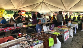 Vendors gather Saturday under a festival tent on the 2500 block of Martin Luther King Avenue SE to raise awareness about Juneteenth, community-building and faith organizations in D.C. (Darla Dunning / The Washington Times)