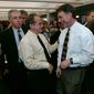 Reporter Kevin Cullen (left) looks on as Boston Globe editor Martin Baron, center, congratulates reporter Stephen Kurkjian, second from left, after the newspaper was awarded a Pulitzer Prize in Boston, Monday April 7, 2003.  The Globe was given a Pulitzer for public service for its coverage of the church abuse scandal that rocked the Boston archdiocese. From left are Cullen, Kurkjian, Baron, Ben Bradlee Jr., Thomas Farragher, Walter Robinson and Sacha Pfeiffer. (Associated Press)