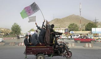 Taliban fighters and their supporters carry a representation of the Afghan national flag and a Taliban flag while riding in a motorized vehicle, in Kabul, Afghanistan, Sunday, June 17, 2018. A suicide bomber struck Sunday in Afghanistan's eastern city of Jalalabad, killing at least 18 people in the second attack in as many days targeting Taliban fighters, security forces and civilians celebrating a holiday cease-fire. (AP Photo/Massoud Hossaini)