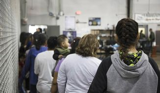 In this photo provided by U.S. Customs and Border Protection, people who've been taken into custody related to cases of illegal entry into the United States, stand in line at a facility in McAllen, Texas, Sunday, June 17, 2018. (U.S. Customs and Border Protection's Rio Grande Valley Sector via AP)