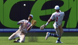 Washington Nationals center fielder Michael Taylor (3) catches a ball hit by Toronto Blue Jays' Aledmys Diaz as Nationals' Wilmer Difo (1) looks on during seventh-inning baseball game action in Toronto, Sunday, June 17, 2018. (Frank Gunn/The Canadian Press via AP)