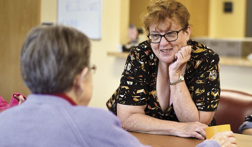 Jean Hinderer, activities director, plays a dice game with elders at Circles of Caring Adult Day Services on Tuesday, June 5, 2018, in Pullman, Wash. (Luke Hollister/The Moscow-Pullman Daily News via AP)