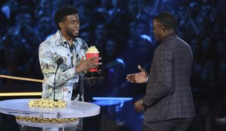 "In this Saturday, June 16, 2018, photo, Chadwick Boseman, left, gives his best hero award for his role in ""Black Panther"" to James Shaw Jr., who is credited with saving lives during a shooting at a Waffle House in Antioch, Tenn., at the MTV Movie and TV Awards at the Barker Hangar on Saturday, June 16, 2018, in Santa Monica, Calif. (Photo by Matt Sayles/Invision/AP)"