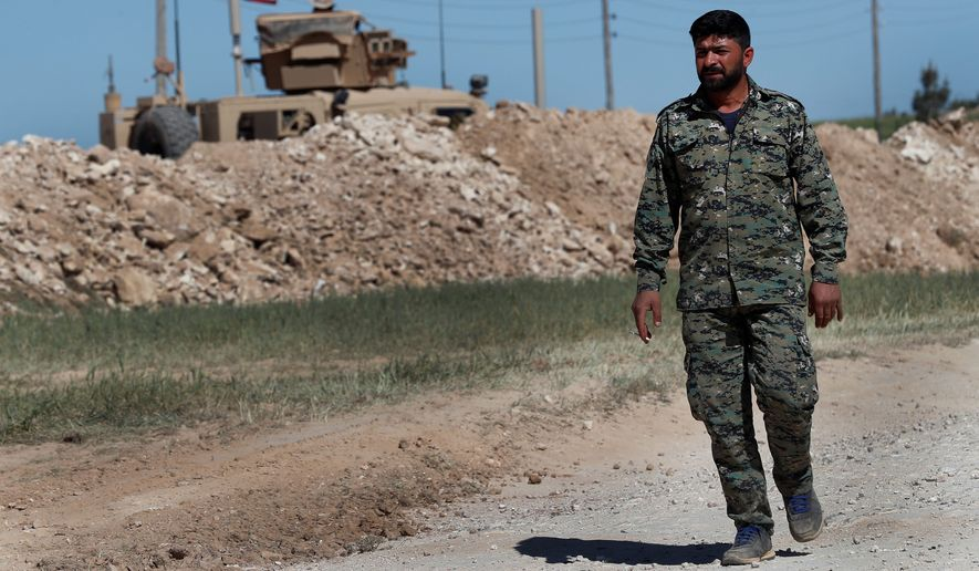 A U.S-backed Syrian Manbij Military Council soldier passes a U.S. position near the tense front line with Turkish-backed fighters. (Associated Press/File)