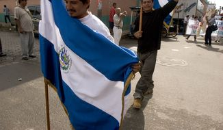 Central American migrants carry a flags of El Salvador and Honduras during a celebration of National Migrant Day at the Suchiate River on the border of Guatemala and Mexico on Sunday Sep. 3, 2006. (AP Photo/Moises Castillo)