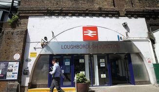 A man walks past Loughborough Junction railway station in south London, Monday June 18, 2018. British Transport Police say three people have died after being struck by a train in south London. Details about the deaths are not yet clear. (Yui Mok/PA via AP)