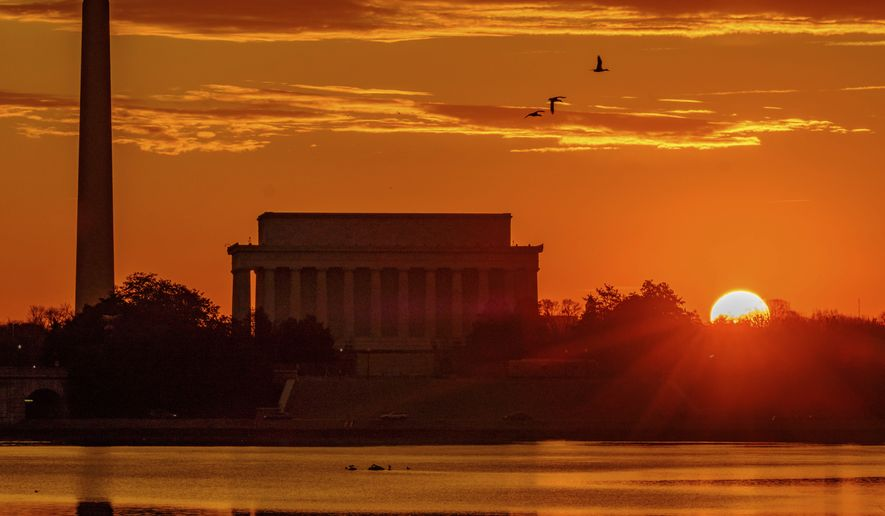 In this Tuesday, March 6, 2018, photo, the sun peaks over the horizon next to the Washington Monument and Lincoln Memorial at daybreak along the Potomac River in Washington. (AP Photo/J. David Ake) **FILE**
