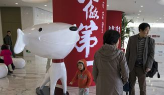 """In this Nov. 11, 2017, photo, a child stands near the mascot for Chinese e-commerce giant JD.com and the words for """"Be Number One"""" at the headquarters in Beijing, China. Google says Monday, June 18, 2018, it will invest $550 million in Alibaba's main rival JD.com as the U.S. tech giant seeks to expand in fast-growing Asian e-commerce markets. (AP Photo/Ng Han Guan)"""