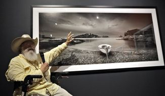 """Clyde Butcher gestures as he gives a description of one of his photographs during the opening of his """"Clyde Butcher, Visions of Dali's Spain"""" exhibit, at the Salvador Dali Museum Friday, June 15, 2018, in St. Petersburg, Fla. The new exhibit features photographs of the places in Spain where Dali lived, shot by Butcher, a photographer renowned for his pictures of the Florida Everglades. (AP Photo/Chris O'Meara)"""