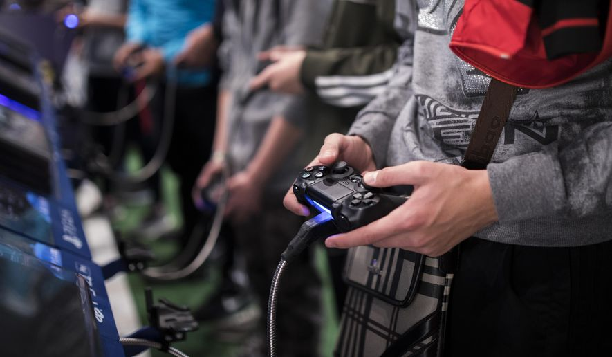 In this Friday, Nov. 3, 2017, file photo, a man plays a game at the Paris Games Week in Paris. The World Health Organization says that compulsively playing video games now qualifies as a new mental health condition, in a move that some critics warn may risk stigmatizing its young players. (AP Photo/Kamil Zihnioglu, File)