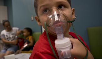 In this May 29, 2018 photo, Yahir Garcia receives one of his two daily treatments for asthma at a medical center in San Juan, Puerto Rico. Garcia is one of many that doctors say are struggling to breathe asthma cases in the U.S. territory spike in the aftermath of the Category 4 storm, raising concerns about deteriorating health conditions on an island struggling to prepare for a new hurricane season. (AP Photo/Ramon Espinosa)