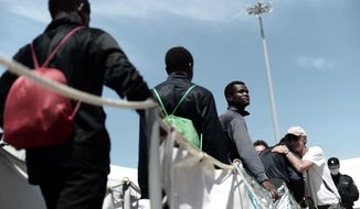 "This photo released on Sunday, June 17, 2018, by French NGO ""SOS Mediterranee"", shows migrants disembarking the SOS Mediterranee's Aquarius ship and MSF (Doctors Without Borders) NGOs, after its arrival at the eastern port of Valencia, Spain. Ships in the Aquarius aid convoy docked Sunday at the Spanish port of Valencia, ending a week long ordeal for hundreds of people who were rescued from the perilous Mediterranean only to become the latest pawn in Europe's battle over immigration. (Kenny Karpov/SOS Mediterranee via AP)"