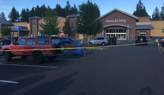 Police officers investigate the scene of a deadly shooting at a Walmart store in Tumwater, Wash., Sunday, June 17, 2018. A gunman wounded a few people before being fatally shot by a bystander at the store in Washington state's city Sunday evening. (KOMO News via AP)