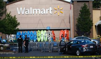 Police investigate the scene of a shooting at a Walmart in Tumwater, Wash., Sunday, June 17, 2018. A gunman injured a teen and shot a man in a pair of carjacking attempts Sunday, before being killed by a bystander outside a Washington state Walmart store. (Bettina Hansen/The Seattle Times via AP)